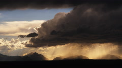 Hurrying dark upslope supercell spilling rain in foreground with lighter clouds Stock Footage