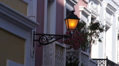 Dimming colonial street light on the side wall of a house in Old San Juan. Stock Footage