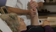 Old woman lying in bed and exercising injured wrist with physiotherapist. Stock Footage