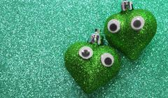 Two big green hearts in love with eyes in the background glitter Stock Photos