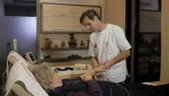 Male physiotherapist doing massage with massager on injured hand of old woman. Stock Footage