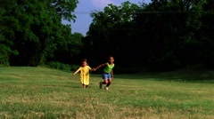Two little girls running hand in hand across grass toward camera Stock Footage