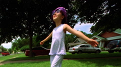 Little girl in fake sunglasses and a purple hat spinning around on a green lawn Stock Footage