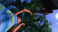 A boy and girl playing pat-a-cake over the up-pointed camera Stock Footage
