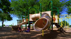 Kids using playground equipment in a park - stock footage