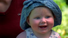 Close-up of a smiling child in a blue hat, smiling mother behind her Stock Footage