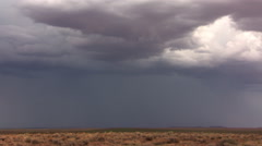 Branched lightning striking from clouds above dry grassland - stock footage
