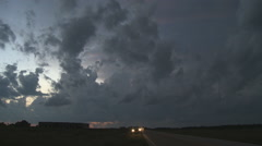 Left pan over dissipating storm clouds over fields along a rural road at evening Stock Footage
