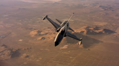 Above a Northrop F-5A supersonic fighter jet flying over desert terrain Stock Footage