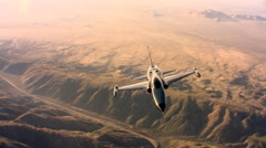 Above a Northrop F-5A supersonic fighter jet flying over rugged desert terrain Stock Footage