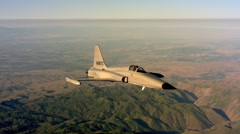 Air-to-air view of Northrop F-5A appearing to hover over rugged terrain - stock footage