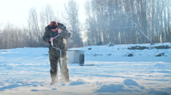 Ice fisherman drill on winter lake Stock Footage