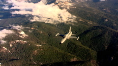 A Northrop F-5A fighter jet flying over a forested mountain does a roll - stock footage
