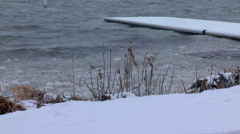 Snow-covered dock beside an icy lake - stock footage
