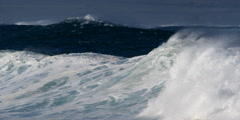 Foaming waves trailing spray as they rush toward dark rocks - stock footage