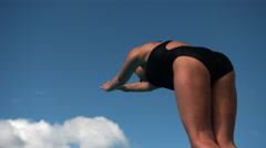 Ultra-slow motion shot of female diver in somersault tuck position against blue Stock Footage