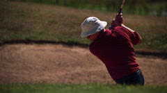 Golfer lofting ball out of a sand trap in ultra-slow motion Stock Footage