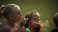Faces of two little girls blowing ultra-slow motion soap bubbles - stock footage