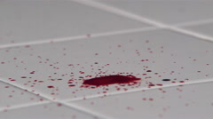 Blood drops falling onto white tile in ultra-slow motion Stock Footage