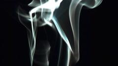 Smoke wisps drifting upward in ultra-slow motion on black frame Stock Footage