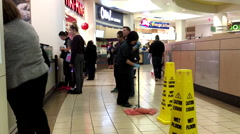 People ordering food and worker cleaning floor at food court area Stock Footage