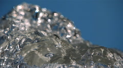 Close-up ultra-slow motion water gushing and receding on blue frame - stock footage