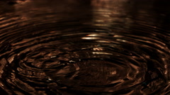 Ultra-slow motion blue-green drops splashing onto bronze-colored ripples - stock footage