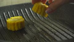 Female hand placing corn cob pieces on hot grill pan - stock footage