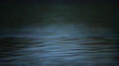 Ultra-slow motion drop flinging bead-like droplets across shadowy green water Stock Footage