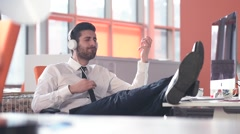 Happy business man at workplace listening music Stock Footage