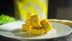 Adding ground pepper and salt to roasted corn cob pieces, 2 videos in 1 Stock Footage