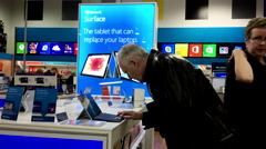 Old man having his reading glasses to try new computer inside Best buy store Stock Footage