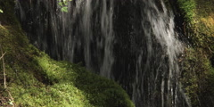 Close-up section of a waterfall streaming over mossy rocks - stock footage