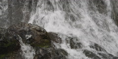 Water streaming over and around boulders below a falls - stock footage