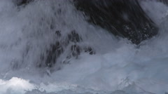Close-up whitewater plunging around a rock - stock footage
