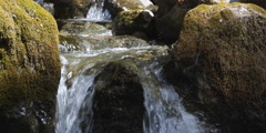Stream cascading over terraced ledges framed by mossy boulders Stock Footage