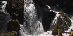 A waterfall with many channels flowing over and around mossy boulders Stock Footage