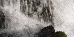 Close-up waterfall plunging and splashing  onto mossy rocks - stock footage