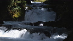 A shaded mountain stream plunging in whitewater stair-steps through its canyon - stock footage