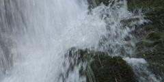 Close-up water at the foot of a falls pelting mossy boulders Stock Footage