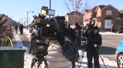 TV news cameras at crime scene gathering for scrum with police Stock Footage