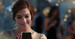 Beautiful girl dressed in gold using smartphone Stock Footage