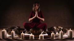 Woman playing Tibetan singing bowls indoors - stock footage