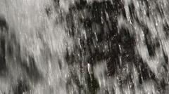 Close-up section of a waterfall streaming over black rock - stock footage