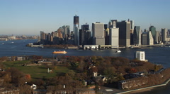 Flying across the tip of Governor's Island toward Lower Manhattan Financial Stock Footage