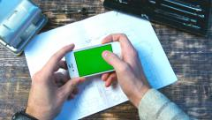 Man using smart phone on wood table w/various hand gestures, horizontal Stock Footage