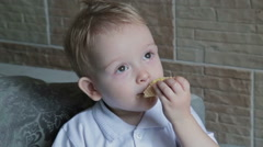 Little beautiful blond boy eating wafer at the kitchen Stock Footage