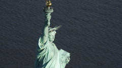 Close flight past the Statue of Liberty above autumn trees on Liberty Island. - stock footage