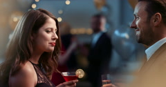 Sexy young couple meet at glamorous party drinking champagne cocktails - stock footage