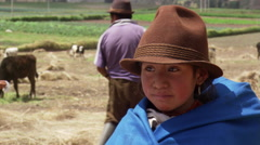 Ecuadorean farm girl in brown hat; adults feeding cattle in background Stock Footage